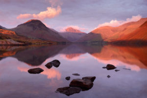 Intense red light from sunset hits the peaks of Yewbarrow, Great Gable and Lingmell on an autumn afternoon at Wast Water in the Lake District.